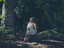 Mulher que senta-se na floresta do início de uma sessão Fotos de Stock Royalty Free