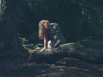 Mulher que senta-se na floresta do início de uma sessão Foto de Stock Royalty Free