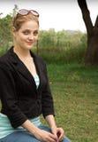 Mulher que senta-se na grama Foto de Stock Royalty Free