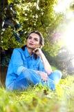 Mulher que senta-se na grama Fotos de Stock