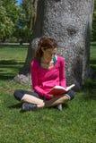 Mulher que senta-se na grama ao lado do livro de leitura da árvore Imagens de Stock Royalty Free