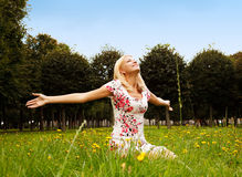 A mulher que senta-se na grama e aprecia o sol Fotos de Stock
