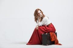 Mulher que senta-se na mala de viagem, isolado, branca Imagens de Stock Royalty Free