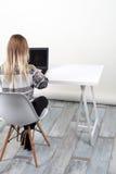 Mulher que senta-se na mesa com portátil Foto de Stock Royalty Free