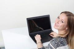 Mulher que senta-se na mesa com portátil Imagem de Stock