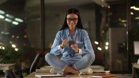 Mulher que senta-se na mesa de escritório, usando o telefone celular, excitado com aplicação móvel vídeos de arquivo