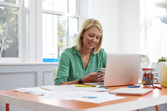 Mulher que senta-se na mesa usando o telefone celular no escritório domiciliário fotos de stock