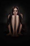 Mulher que senta-se na obscuridade Fotografia de Stock Royalty Free