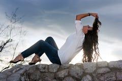 Mulher que senta-se na parede imagens de stock royalty free