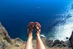 Mulher que senta-se na parte superior com seus pés sobre a superfície do mar da cor azul agradável Imagem de Stock