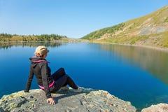 Mulher que senta-se na pedra Imagens de Stock