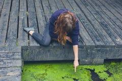 Mulher que senta-se na plataforma pela lagoa na floresta fotos de stock royalty free