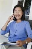 Mulher que senta-se na poltrona, falando no móbil Fotografia de Stock