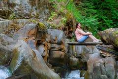 Mulher que senta-se na ponte de madeira Foto de Stock