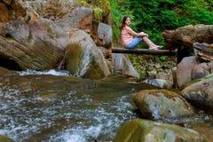 Mulher que senta-se na ponte de madeira Imagens de Stock Royalty Free
