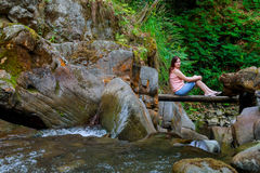 Mulher que senta-se na ponte de madeira Foto de Stock Royalty Free