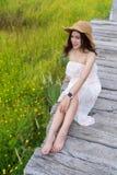 Mulher que senta-se na ponte de madeira com campo de flor amarelo do cosmos imagem de stock