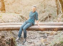 Mulher que senta-se na ponte pequena na floresta fotografia de stock royalty free