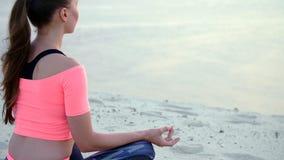 Mulher que senta-se na pose da ioga do abrandamento na praia do mar closeup filme