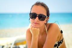 Mulher que senta-se na praia Fotos de Stock Royalty Free