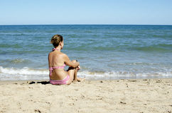 Mulher que senta-se na praia Imagens de Stock Royalty Free