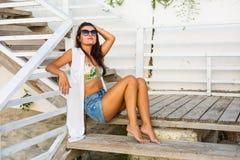 Mulher que senta-se na praia Fotografia de Stock