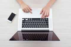 Mulher que senta-se na retina de MacBook Pro e no iPhone 5s Fotos de Stock