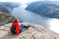 Mulher que senta-se na rocha do púlpito/Preikestolen, Noruega Fotos de Stock Royalty Free