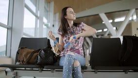 Mulher que senta-se na sala de espera do aeroporto e de seu cabelo filme