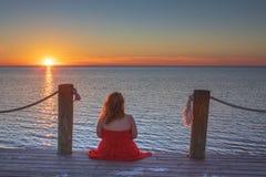 Mulher que senta-se na salva de observação NC do por do sol da doca imagem de stock