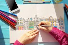 Mulher que senta-se na tabela com o livro para colorir para adultos fotografia de stock royalty free