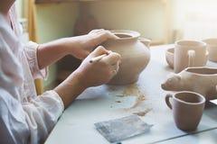 Mulher que senta-se na tabela que faz a cerâmica fotos de stock royalty free