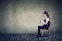 Mulher que senta-se na tabela imaginária imagens de stock royalty free