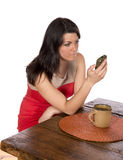 Mulher que senta-se na tabela no telemóvel fotografia de stock