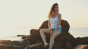 Mulher que senta-se nas rochas que olham fixamente para fora em um corpo de água filme