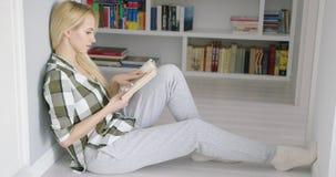Mulher que senta-se no assoalho com livro filme