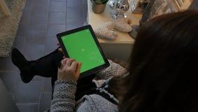 Mulher que senta-se no assoalho e que usa o tablet pc vertical com tela verde Feche acima do tiro das mãos do ` s da mulher com a filme