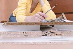 Mulher que senta-se no assoalho em casa e na mob?lia de montagem usando ferramentas da m?o fotografia de stock