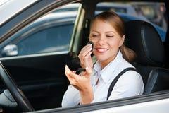 A mulher que senta-se no automóvel e que aplica-se compo Imagens de Stock Royalty Free