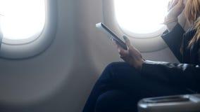 Mulher que senta-se no avião do conforto com tabuleta filme