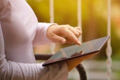 Mulher que senta-se no balcão e que usa o tablet pc digital fotografia de stock royalty free