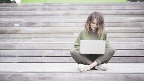 Mulher que senta-se no banco ao datilografar no portátil Fundo de madeira Imagens de Stock