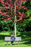 Mulher que senta-se no banco de parque que lê um livro imagem de stock royalty free