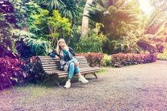Mulher que senta-se no banco no parque do jardim botânico Fotos de Stock