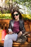 Mulher que senta-se no banco usando o móbil foto de stock royalty free