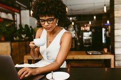 Mulher que senta-se no café com um portátil fotografia de stock royalty free