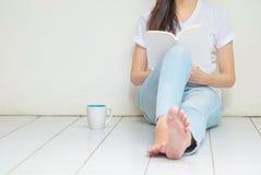 A mulher que senta-se no canto da casa para ler um livro no tempo livre na tarde, relaxa a época da mulher asiática fotos de stock royalty free