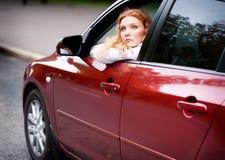 Mulher que senta-se no carro foto de stock