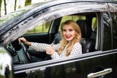 Mulher que senta-se no carro e que mostra os polegares acima na estrada Fotos de Stock Royalty Free