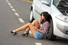 Mulher que senta-se no carro quebrado próximo à terra Fotos de Stock Royalty Free